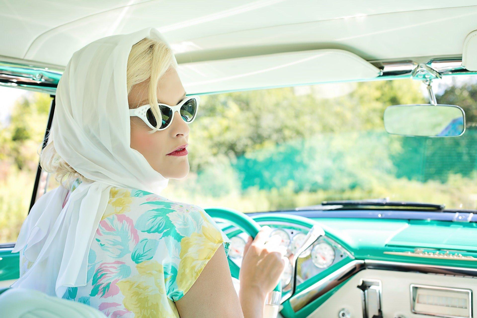 Mujer vintage conduciendo con gafas de sol y pañuelo